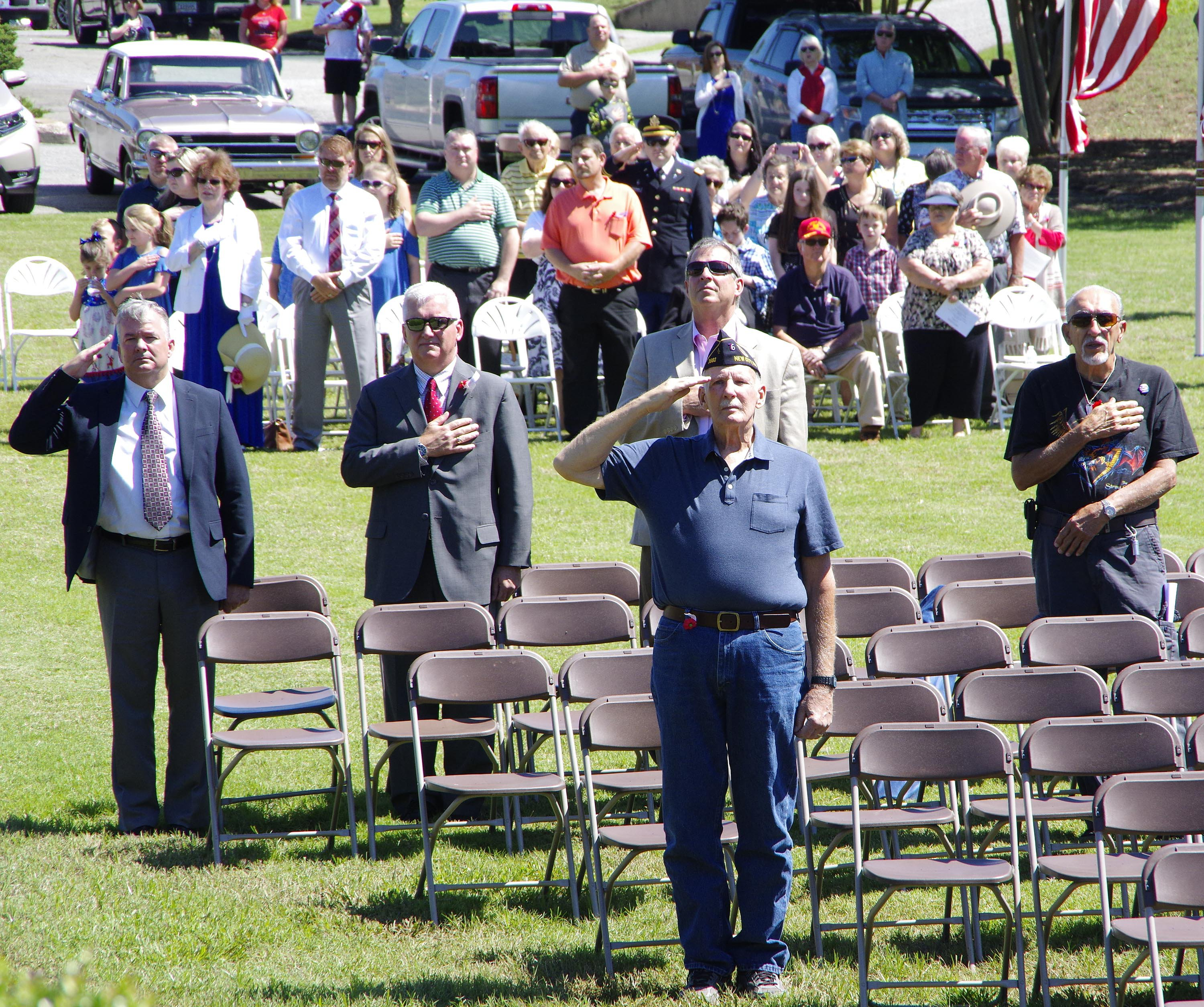 Veterans in the audience salute as the colors pass by.