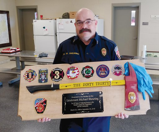 Lt Michael Sheuring poses with a display piece created by his fellow firefighters.jpg